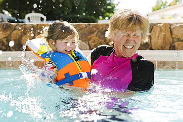 Grandmother playing with toddler girl (2-3) in outdoors swimming pool