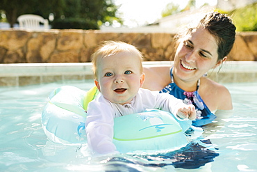 Mother with baby son (6-11months) playing in outdoor swimming pool