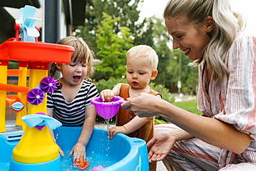 Mother with baby son (18-23 months) and toddler daughter(2-3)playing with water in garden
