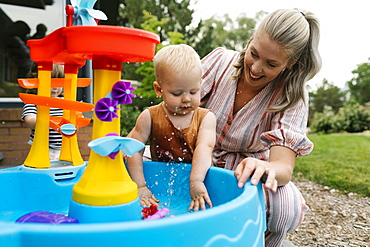 Mother with baby son (18-23 months) playing with water in garden