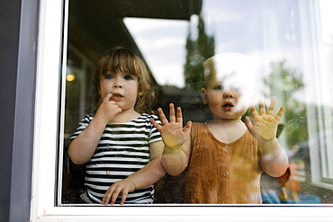 Portrait of toddler girl (2-3) and baby boy (18-23 months) standing behind window