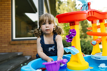 Portrait of toddler girl (2-3) playing with water in garden