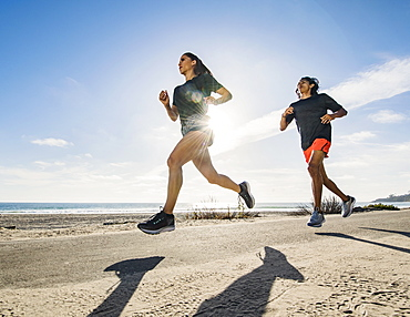 USA, California, Dana Point, Man and woman running together by coastline