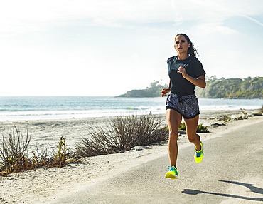 USA, California, Dana Point, Woman running on road by coastline