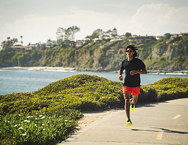 USA, California, Dana Point, Man running on road by coastline