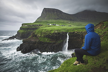 Denmark, Faroe Islands, Gasadalur Village, Mulafossur Waterfall, Man sitting on edge of cliff and looking at Mulafossur Waterfall