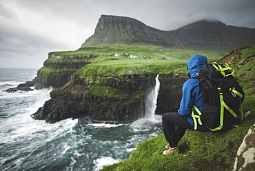 Denmark, Faroe Islands, Gasadalur Village, Mulafossur Waterfall, Man with backpack sitting on edge of cliff and looking at Mulafossur Waterfall