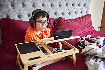 Boy (8-9) gaming on tablet while sitting in bed during weekend