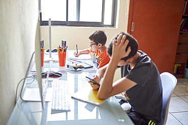 Two boys (8-9, 14-15) learning at desk at home during Covid-19 lockdown