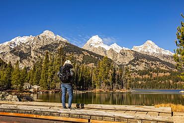 USA, Wyoming, Jackson, Grand Teton National Park, Senior woman standing by Taggart Lake in Grand Teton National Park