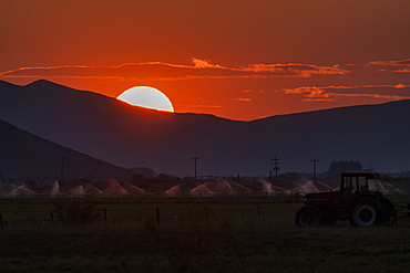 USA, Idaho, Bellevue, Irrigation equipment in field and sun setting behind mountain