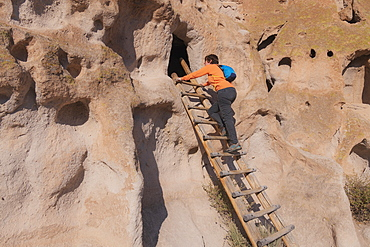 USA, New Mexico, Bandelier National Monument, Woman climbing ladder to cliff dwellings in Bandelier National Monument
