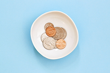 Coins in bowl on blue background