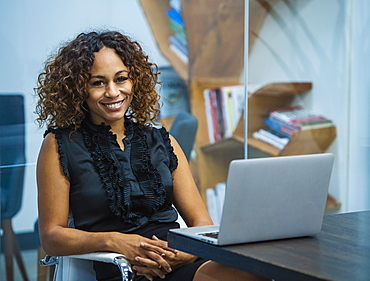 Portrait of smiling businesswoman sitting at desk in office