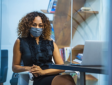 Portrait of businesswoman wearing face mask sitting at desk in office