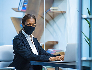 Portrait of businesswoman wearing face mask working on laptop at desk in office