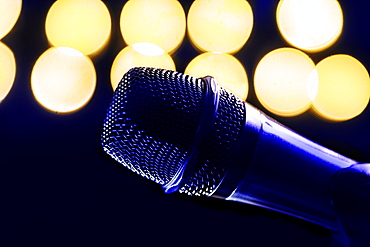 Close-up of microphone and stage lights