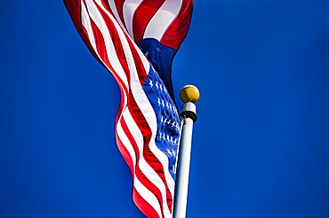 American flag blowing in wind against blue sky