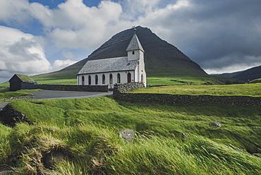 Denmark, Faroe Islands, Vidareidi, Green landscape with rural church and mountain