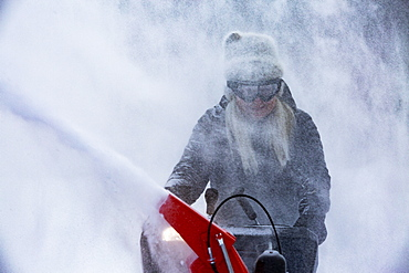Senior woman clearing snow using snowblower