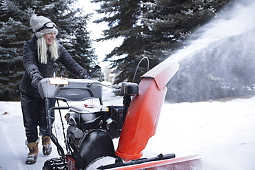 USA, Idaho, Bellevue, Senior woman clearing snow using snowblower
