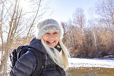 USA, Idaho, Sun Valley, Winter portrait of smiling woman hiking along river