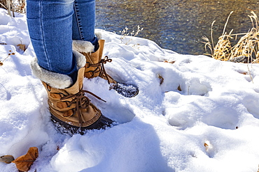 Legs of senior woman in hiking boots standing in snow