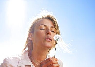 Blond woman blowing dandelion