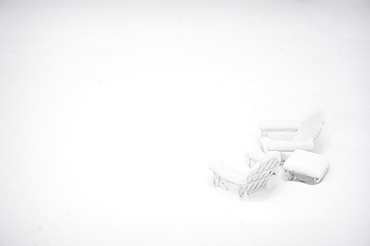 Outdoor chairs and table covered with snow