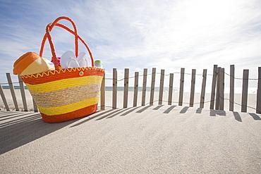Beach bag with flip-flops on beach