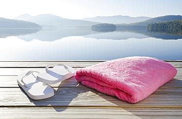 USA, New York, North Elba, Lake Placid, Sandals and towel on dock