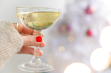 Hand holding champagne glass next to Christmas tree