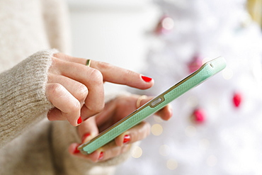 Hands holding smartphone next to Christmas tree