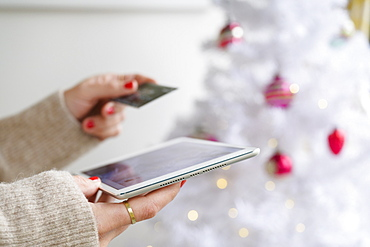 Hands holding tablet and credit card next to Christmas tree