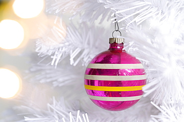 Pink ornament on white Christmas tree