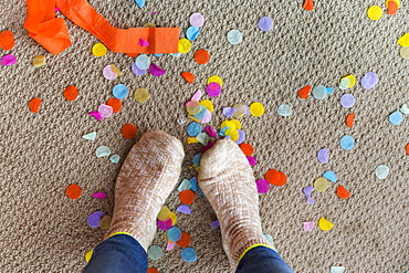 Human feet on floor with confetti