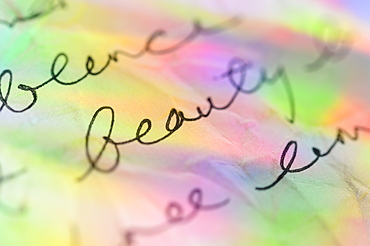 Handwriting on paper with colorful reflections