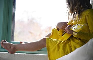 Girl (8-9) playing ukulele by window