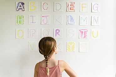 Rear view of girl (8-9) looking at alphabet on wall