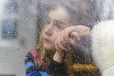 Close-up of girl (8-9) looking through window on rainy day