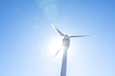 Low angle view of wind turbine against blue sky and sun