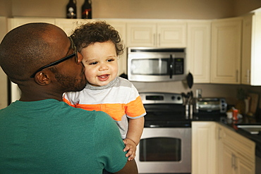 Father kissing baby in kitchen