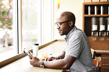 Black man using digital tablet in coffee shop