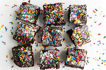 Overhead view of freshly baked brownies covered with colorful sprinkles