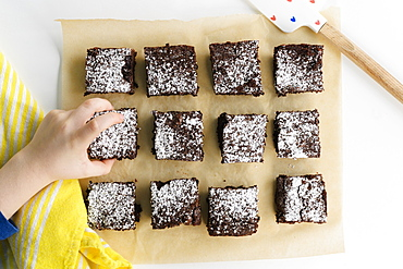 Overhead view of boys (6-7) hand reaching for freshly baked brownie