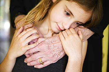 Close-up of grandmothers hand embracing granddaughter (8-9)