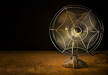 Old metal electric fan on wooden table