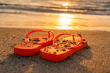 United States, Florida, Boca Raton, Flip flops on beach at sunset