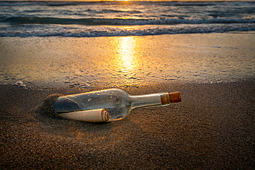 United States, Florida, Boca Raton, Glass bottle with message inside on beach at sunset