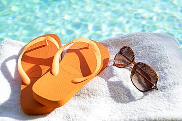 Orange flip flops and sunglasses on towel at poolside